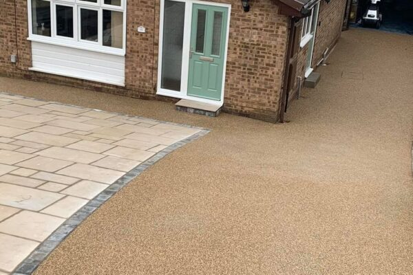 A stone patio with a modern resin bound driveway